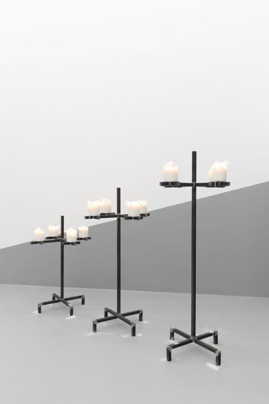 Steel, black paint, white candles – 3 elements \r<br>102 h x ⌀ 44 cm / 83,5 h x ⌀ 44 cm / 65 h x ⌀ 44 cm \r\n\r\nPhoto: CHROMA, courtesy Galerie Gilla Loercher